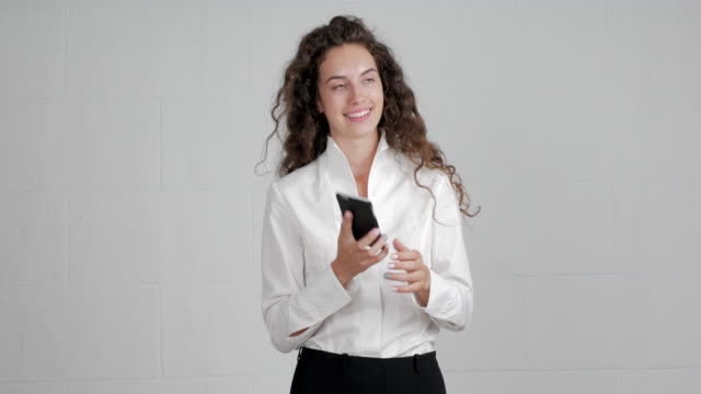 beautiful businesswoman brings a smartphone to her head and begins to speak on a green background - blouse stock videos & royalty-free footage