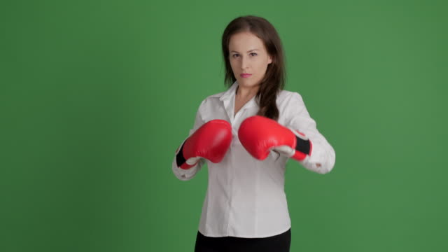 beautiful businesswoman in boxing gloves funny shows her victory in a duel on a green background - boxing glove stock videos & royalty-free footage