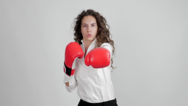 beautiful businesswoman in boxing gloves funny shows her victory in a duel on a white background - blouse stock videos & royalty-free footage