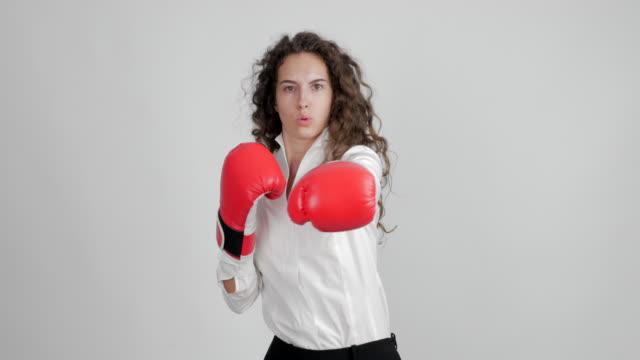 schöne geschäftsfrau in boxhandschuhen lustige zeigt ihren sieg in einem duell auf weißem hintergrund - bluse stock-videos und b-roll-filmmaterial