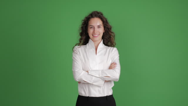 beautiful businesswoman looking with a smile at the camera with her hands crossed on a green background - green colour stock videos & royalty-free footage