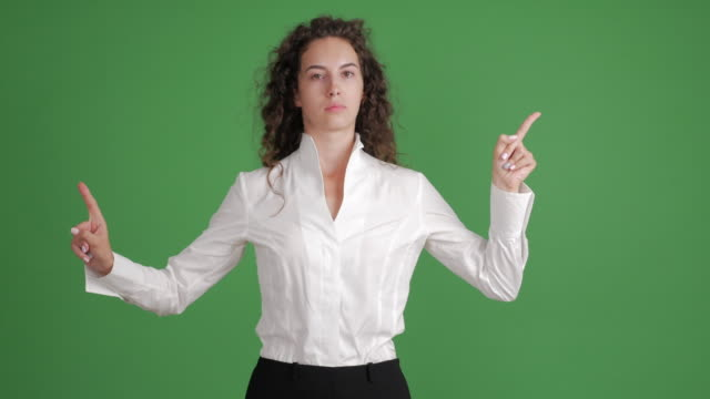 beautiful businesswoman showing copy space and showing a taboo on a green background - blouse stock videos & royalty-free footage