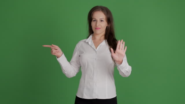 beautiful businesswoman showing copy space  and showing taboo on green background - blouse stock videos & royalty-free footage