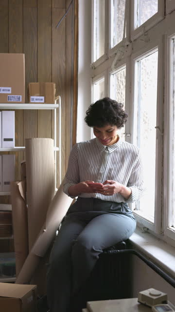 beautiful businesswoman sitting by the window and using her smart phone - sitting stock videos & royalty-free footage