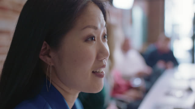 cu beautiful businesswoman softly smiles as she talks to a fellow employee - side view stock videos & royalty-free footage