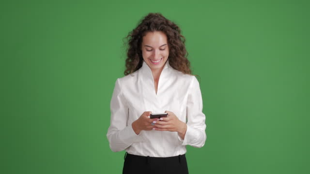 beautiful businesswoman uses to write messages on a smartphone on a green background - scontornabile video stock e b–roll