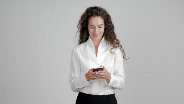 beautiful businesswoman uses to write messages on a smartphone on a white background - waist stock videos & royalty-free footage