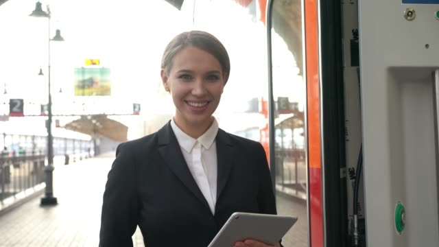beautiful cabin crew member standing at the entrance of the train smiling at camera while holding a tablet - ferrovia video stock e b–roll