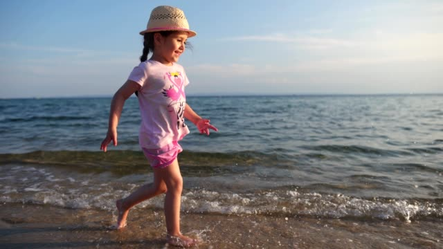 beautiful candid child showing her love for the sea and the beach - water's edge stock videos & royalty-free footage