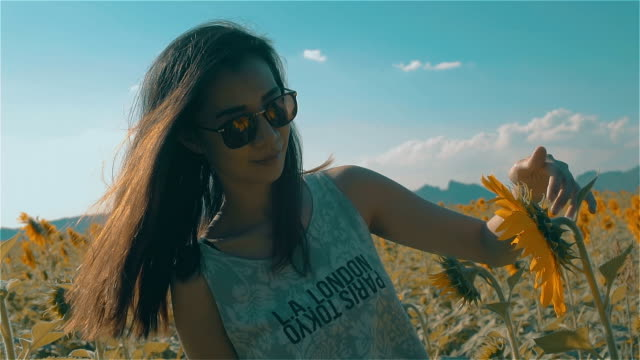 Beautiful Carefree Asian Young Woman touches hand to Sunflowers