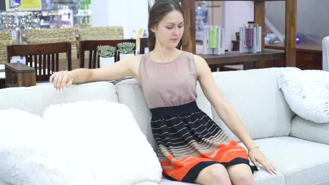 beautiful carefree woman chooses sofa - furniture stock videos & royalty-free footage