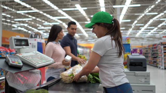 vídeos de stock, filmes e b-roll de caixa bonita que registra produtos na verificação geral para o par do cliente no supermercado - título de eleitor