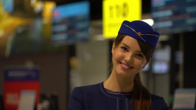 vídeos de stock, filmes e b-roll de atendente de vôo caucasiano bonito que sorri na câmera muito alegremente - tripulação de bordo