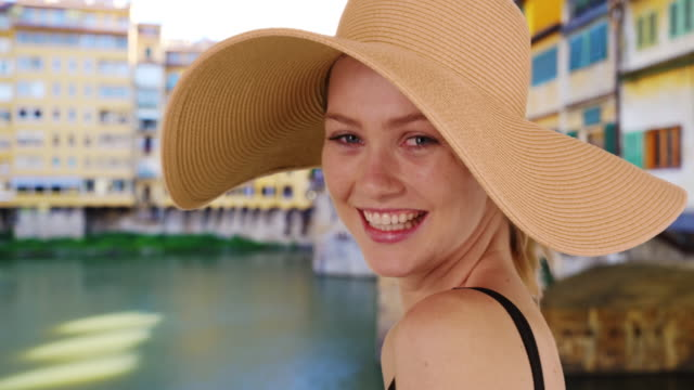 beautiful caucasian girl by the ponte vecchio bridge wearing sunhat - ponte点の映像素材/bロール