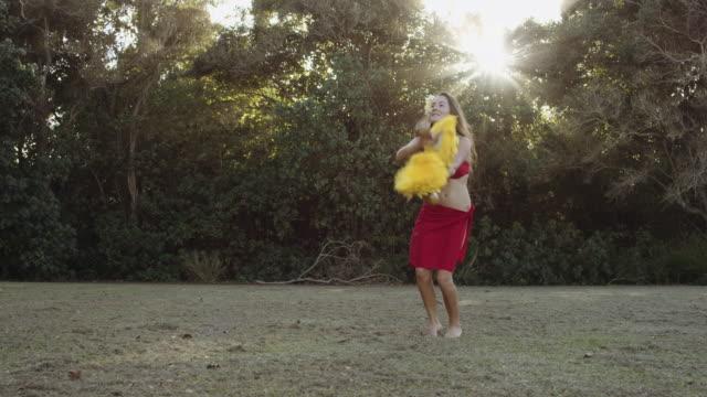 vídeos de stock, filmes e b-roll de dançarina de hula de caucasiano linda realizando em um campo - cultura do havaí