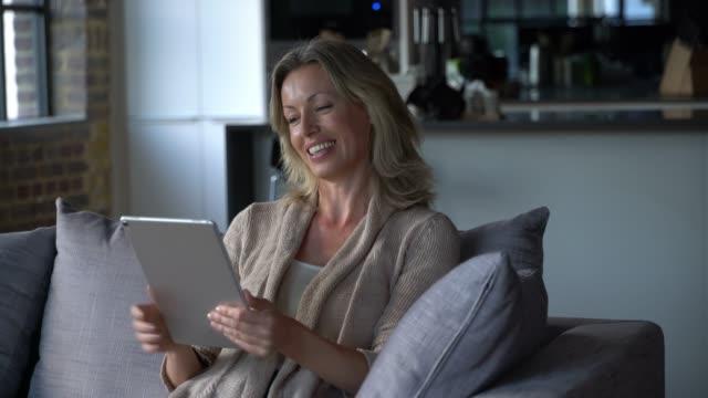 stockvideo's en b-roll-footage met mooie kaukasische vrouw thuis op een video-oproep met behulp van een tablet praten en glimlachen - alleen één oudere vrouw