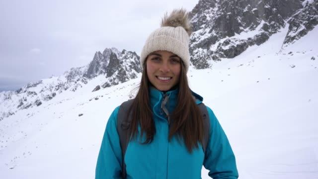 Beautiful caucasian woman facing camera smiling while hiking at the alps