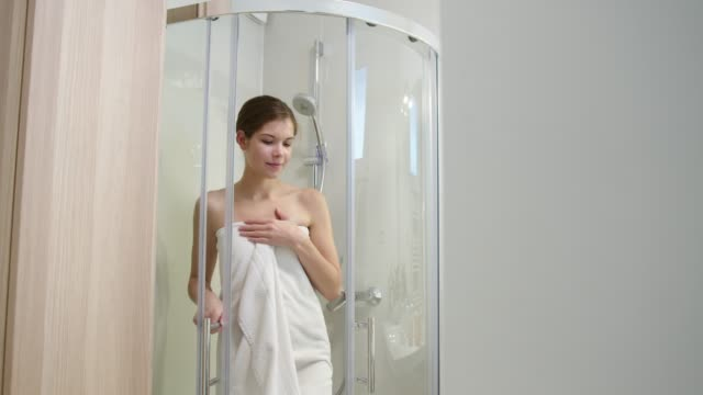 beautiful caucasian woman getting out of the shower wrapped in a white towel - wrapped in a towel stock videos & royalty-free footage