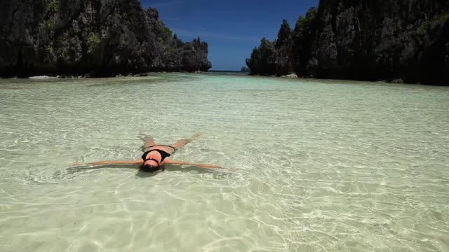WS, beautiful caucasian woman in bikini floating in tropical waters in secluded lagoon / Matinloc Island, Bacuit Archipelago, El Nido, Palawan, Philippines