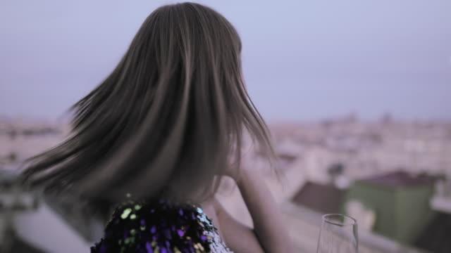vídeos de stock e filmes b-roll de beautiful caucasian woman in cocktail dress on rooftop adjust hair - elegância