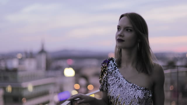 beautiful caucasian woman in cocktail dress on rooftop looking at view - cocktail dress stock videos & royalty-free footage