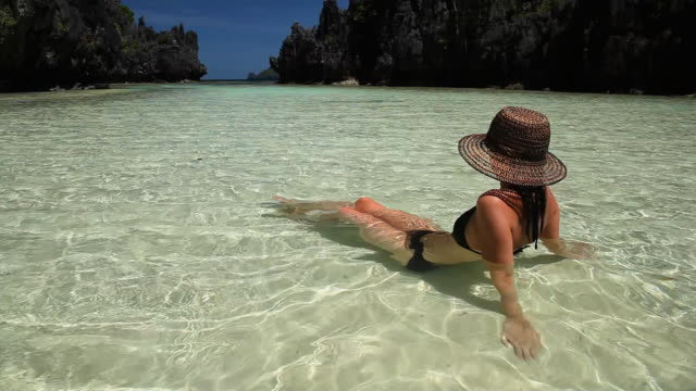 WS, beautiful caucasian woman wearing sun hat relaxing in tropical waters in secluded lagoon / Matinloc Island, Bacuit Archipelago, El Nido, Palawan, Philippines