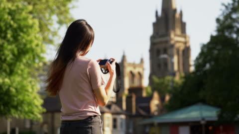 stockvideo's en b-roll-footage met mooie kaukasische vrouwen nemen een foto met camera op park - fotografische thema's