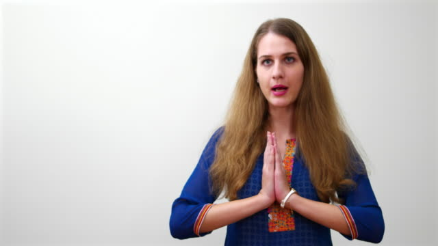 Beautiful cheerful caucasian woman, in Indian attire, joining hands for the Indian 'namaste' greeting