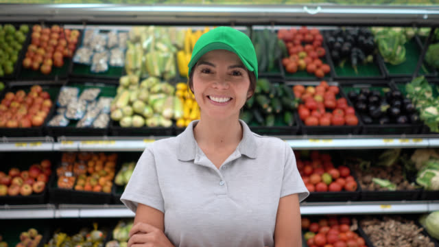 beautiful cheerful manager of a supermarket smiling at camera with arms crossed - shop assistant stock videos & royalty-free footage