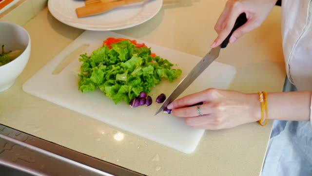 Bello chef prepara le verdure per Insalata biologica