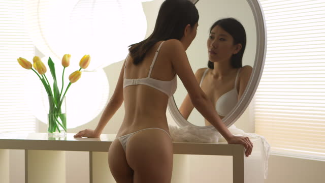 vidéos et rushes de beautiful chinese woman looking through mirror - sensualité