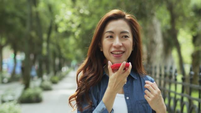 Schöne Chinesin spricht auf Handy an Treelined Street