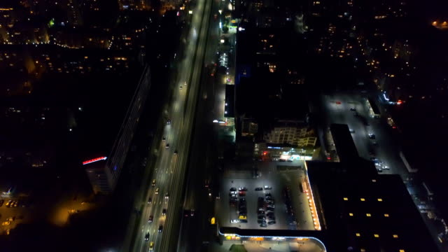 beautiful cinematic aerial reveal shot of capital city central district at night - headlight stock videos & royalty-free footage