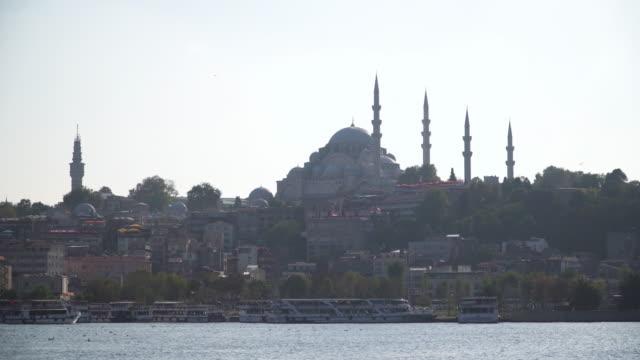 冬の大気汚染の下で黄金の角の近くの公園に沿って歩きながら、イスタンブールのトゥリョール港のウォーターフロントにフェリーボートとエミノヌ地区の観光ランドマークの美しい街並み� - イスタンブール 金角湾点の映像素材/bロール