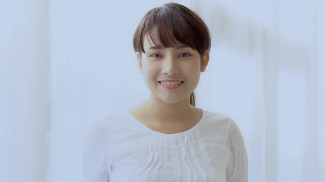 美しいですクローズアップ肖像画若いですアジアの女性とともに笑顔と笑いとともにベッドルーム, 女の子見ていますとともにカメラで幸せと面白い, スローモーション. - 美しい人点の映像素材/bロール