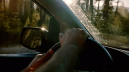 Beautiful close-up shot of two male hands holding car steering wheel driving along forest road in Yosemite slow motion.