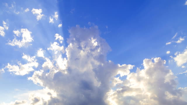 beautiful cloudscape with large, building clouds and sunrise breaking through cloud mass. - sunny stock videos & royalty-free footage