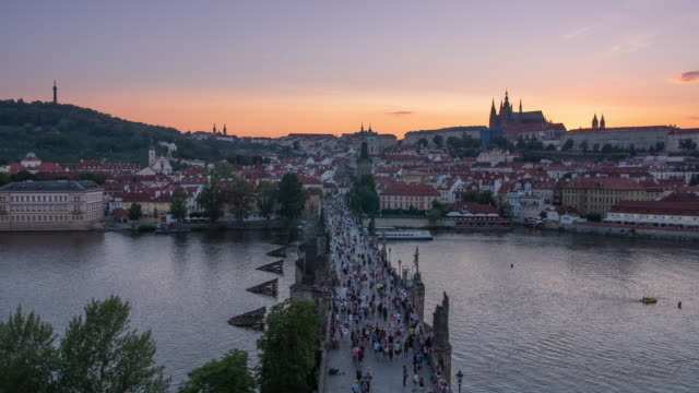 stockvideo's en b-roll-footage met a beautiful colourful sunset timelapse of old town bridge in prague czechoslovakia prague castle can be seen on the horizon - praagse burcht
