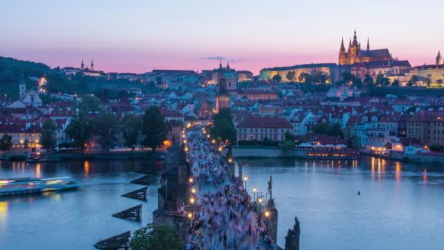vídeos de stock, filmes e b-roll de beautiful colourful sunset timelapse of old town bridge in prague, czechoslovakia. prague castle can be seen on the horizon - praga