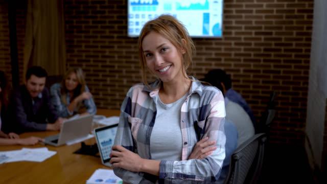 Schöne selbstbewusste Frau mit Arme gekreuzt, Blick auf die Kamera zu Lächeln, während co Arbeiter im Hintergrund arbeiten