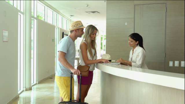 beautiful couple checking in the hotel - hotel stock videos & royalty-free footage