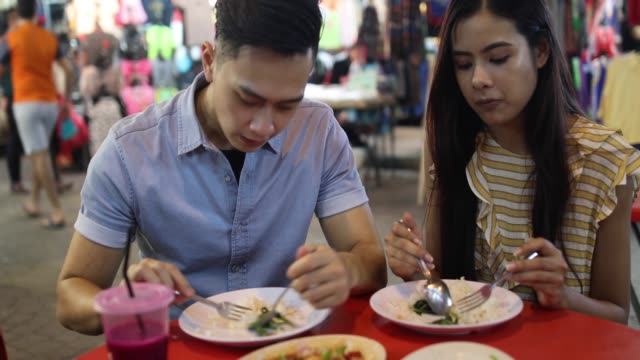 Beautiful couple eating street food