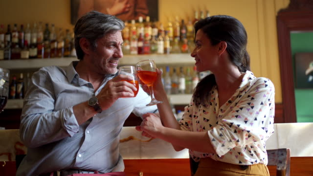 beautiful couple falling in love over drinks at a bar - flirtare video stock e b–roll