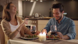 Beautiful Couple Having Candlelight Dinner in the Kitchen. They Eat, Drink and Talk. Both are in Good Mood and Smile a lot. Slow Motion.