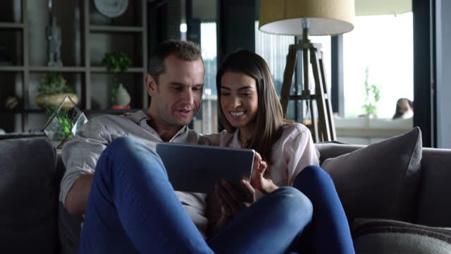 vídeos y material grabado en eventos de stock de hermosa pareja divirtiéndose en casa relax en el sofá mirando algo en la tablet - usar la tableta digital