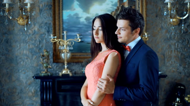 Beautiful couple in elegant evening clothes in classic vintage apartments