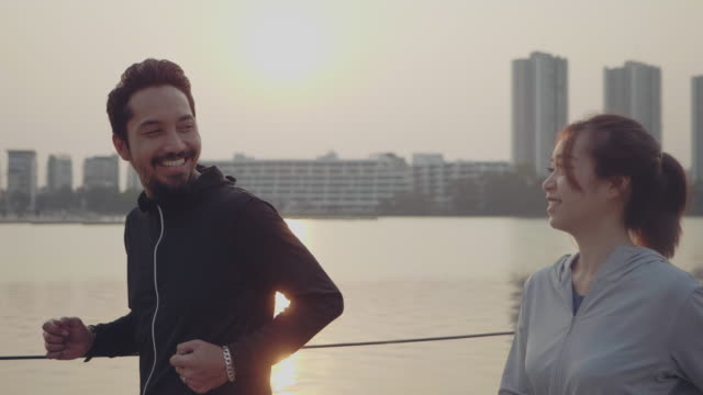 beautiful couple jogging by the lake. - jogging stock videos & royalty-free footage