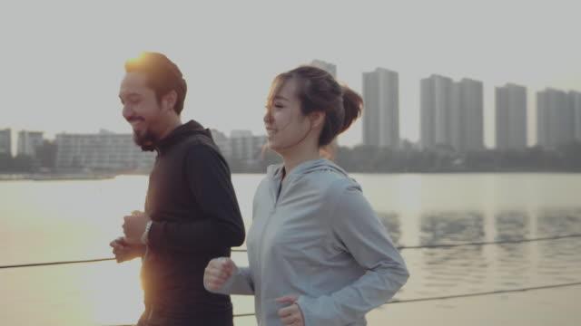 湖のそばでジョギングをする美しいカップル。 - jogging点の映像素材/bロール