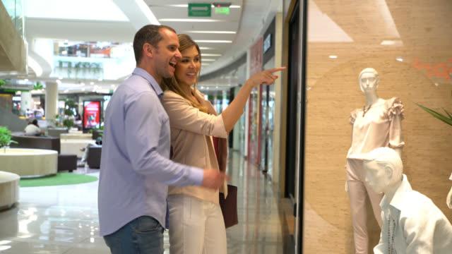 vídeos y material grabado en eventos de stock de hermosa pareja mirando un escaparate de una tienda y luego caminando a la tienda - centro comercial