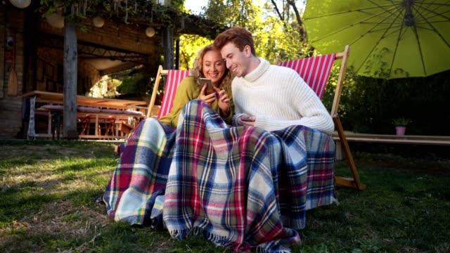 vídeos de stock, filmes e b-roll de lindo casal olhando para meios de comunicação sociais, ao passar o tempo aconchegante juntos ao ar livre - chapéu de sol